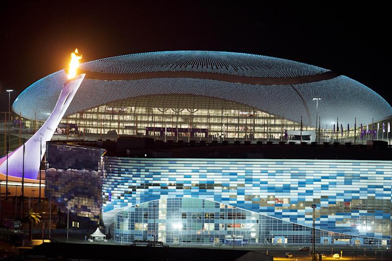 The Olympic Cauldron, left, is lit during a test between the Bolshoy Ice Dome, top, and the Iceberg Skating Palace, foreground, early Thursday morning, Feb. 6, 2014, in Sochi, Russia, prior to the start of the 2014 Winter Olympics. (AP Photo/Pavel Golovkin)