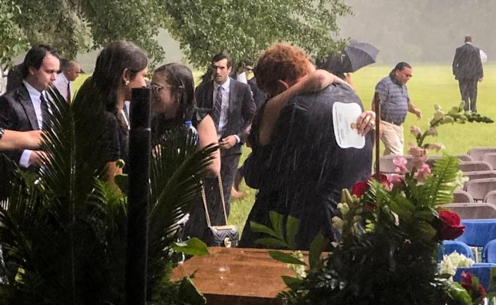 Buster Murdaugh, center, receives a hug in the pouring rain at the funeral service for his brother, Paul, and mother, Maggie, on June 11, 2021.