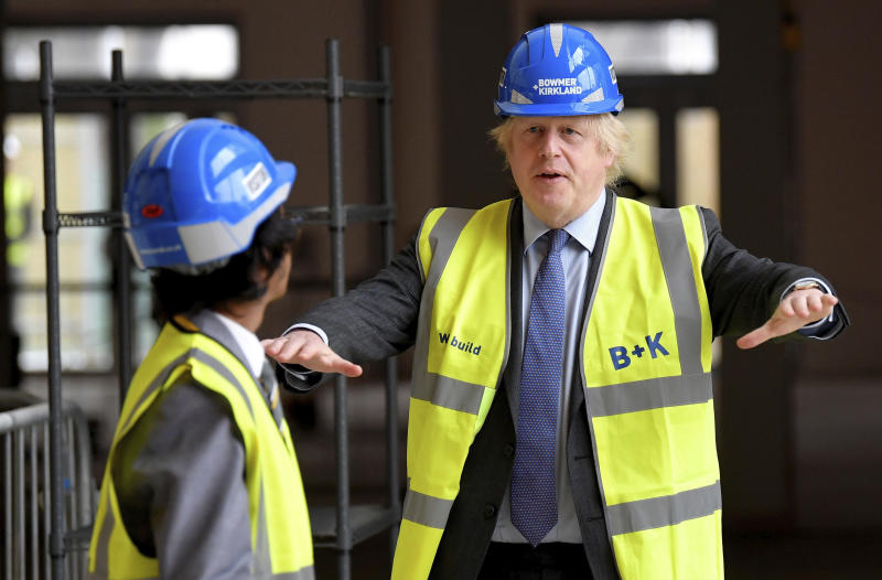 Britain's Prime Minister Boris Johnson talks with year 10 pupil Vedant Jitesh during a visit to the construction site of Ealing Fields High School in west London, Monday June 29, 2020. (Toby Melville/Pool via AP)
