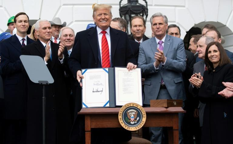 US President Donald Trump holds up the signed United States-Mexico-Canada Trade Agreement, known as USMCA, during a ceremony at the White House in January 2020
