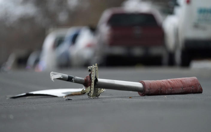 A part from a United Airlines jetliner sits in the middle of Elmwood Street in the street near a home peppered by parts from a plane as it was making an emergency landing at nearby Denver International Airport Saturday, Feb. 20, 2021. (AP Photo/David Zalubowski)