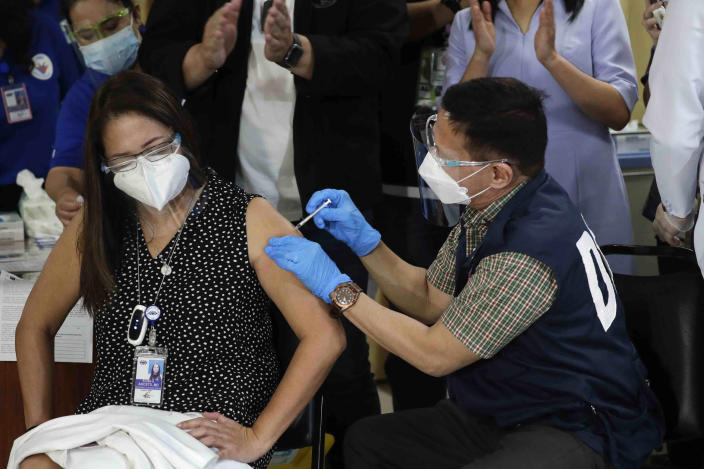 Health Secretary Francisco Duque III, right, injects China's Sinovac vaccine on Filipino doctor Eileen Aniceto during the first batch of vaccination at the Lung Center of the Philippines in Quezon city, Philippines on Monday, March 1, 2021. The Philippines launched a vaccination campaign Monday to contain one of Southeast Asia's worst coronavirus outbreaks but faces supply problems and public resistance, which it hopes to ease by inoculating top officials. (AP Photo/Aaron Favila)