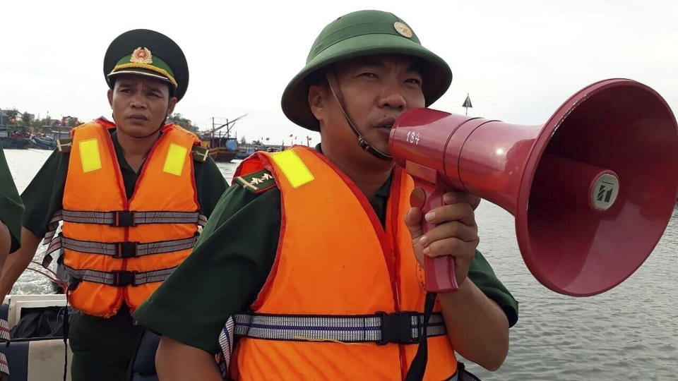 A coast guard officer speaks on a megaphone at a fishing boat shelter in Quang Binh province, Vietnam on Saturday, Nov. 14, 2020. Vietnam's authority has ordered some 460,000 people to be ready for evacuation ahead of Typhoon Vamco reaching the country's central coast. (Nguyen Duc Tho/VNA via AP)