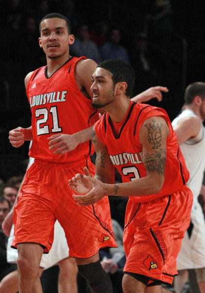 Louisville's Peyton Siva (3) and teammate Jared Swopshire (21) celebrate during the second half of an NCAA college basketball game in the semifinals of the Big East Conference tournament against Notre Dame in New York, Friday, March 9, 2012. Louisville won the game 64-50. (AP Photo/Frank Franklin II)