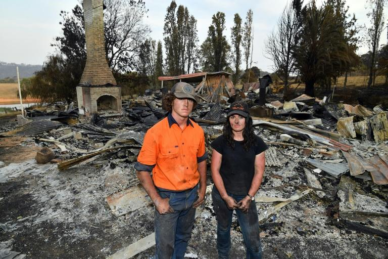 Brother and sisters Jesse and Kiahan Bellchambers stand in front of the charred ruins of their home in Batlow, in Australia's New South Wales state (AFP Photo/SAEED KHAN)