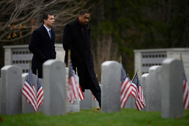 Democratic presidential hopeful Mayor Pete Buttigieg (L) walks through the New Hampshire State Veterans Cemetery in Boscawen, New Hampshire, on Nov. 11, 2019, with fellow veteran Thomas Gary, a senior petty officer at Naval Station Great Lakes, for a Veterans Day service as he continues his 4-day bus tour of the state. (Photo: Jim Watson/AFP via Getty Images)