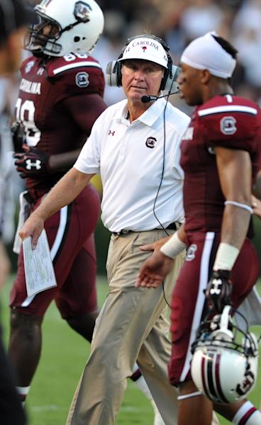 South Carolina head coach Steve Spurrier, center, talks to his team on the sidelines during the first half of an NCAA college football game against North Carolina, Thursday, Aug. 29, 2013, in Columbia, S.C. (AP Photo/Stephen Morton)