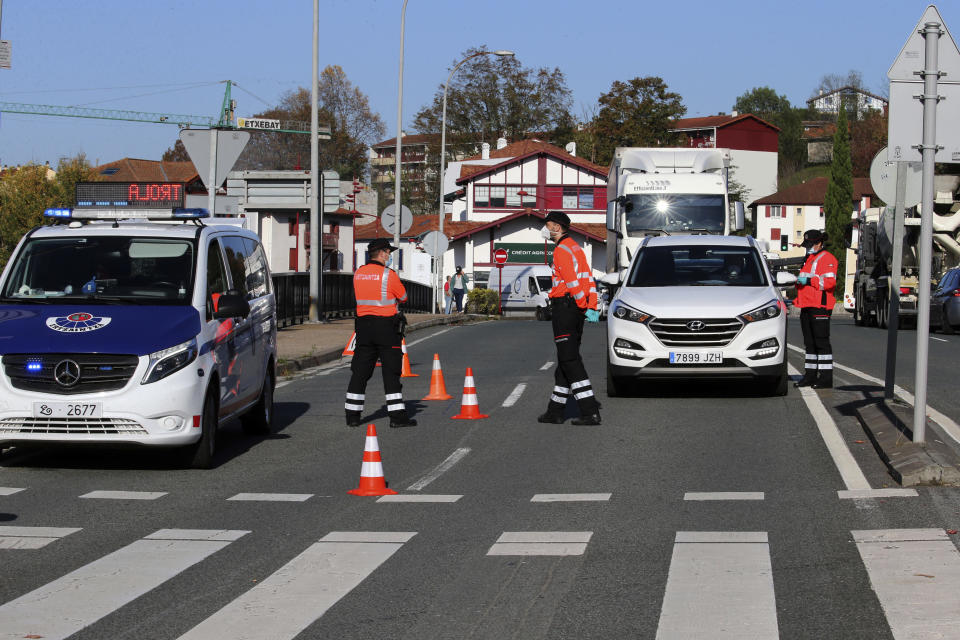 Basque Ertzaintza police officers control cars at French-Spanish border in Behobia, Spain, Friday, Oct. 30, 2020. France re-imposed a monthlong nationwide lockdown Friday aimed at slowing the spread of the virus, closing all non-essential business and forbidding people from going beyond one kilometer from their homes except to go to school or a few other essential reasons. (AP Photo/Bob Edme)