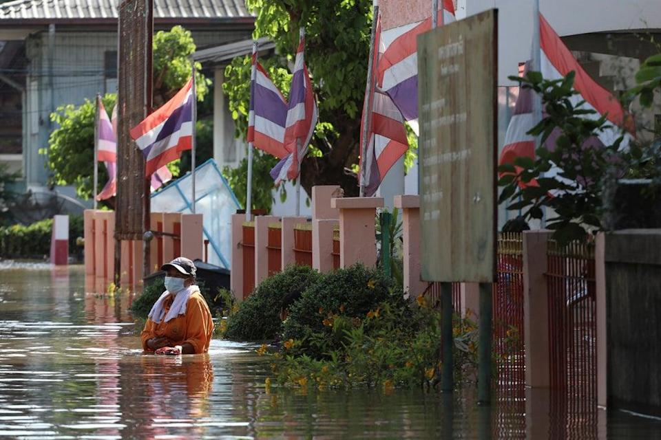 A woman wades through floodwaters in Ayutthaya province, north of Bangkok, Thailand, Monday, October 4, 2021. (AP)