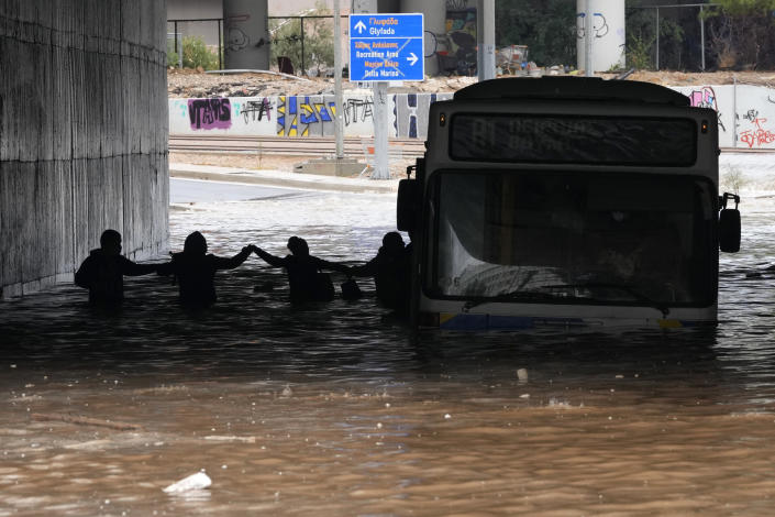 Passengers are silhouetted as they wade through high water after evacuating a bus stuck in a flooded underpass in southern Athens, Thursday, Oct. 14, 2021. Storms have been battering the Greek capital and other parts of southern Greece, causing traffic disruption and some road closures. (AP Photo/Thanassis Stavrakis)