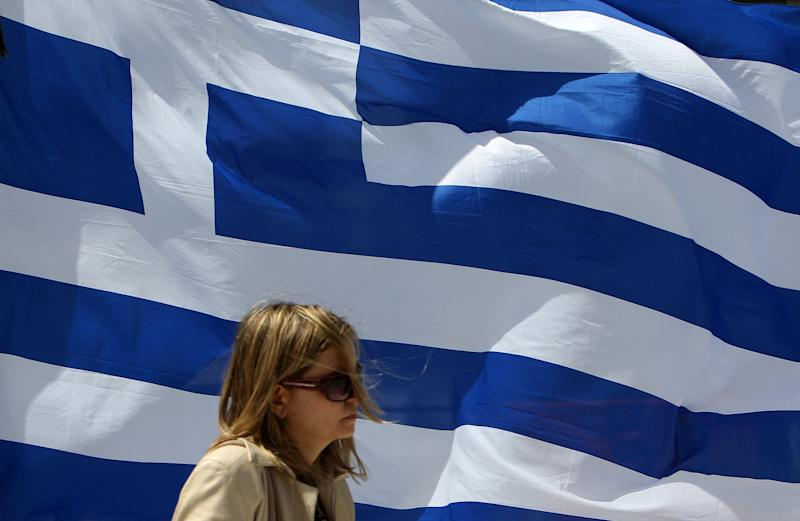 A woman passes in front of a Geek flag in Athens, Friday, April 20, 2012. Polls indicate that Greece's majority Socialists are trailing their main conservative rivals by up to 7 percentage points nearly two weeks before crucial national elections. Voting is scheduled for Sunday, May 6. (AP Photo/Thanassis Stavrakis)