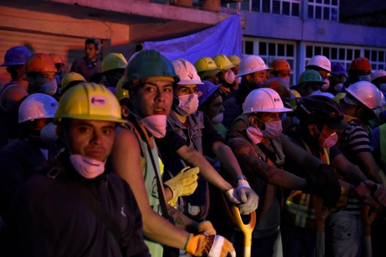Volunteers wait to help with the cleanup of rubble from collapsed buildings as the search for survivors continues in Mexico City