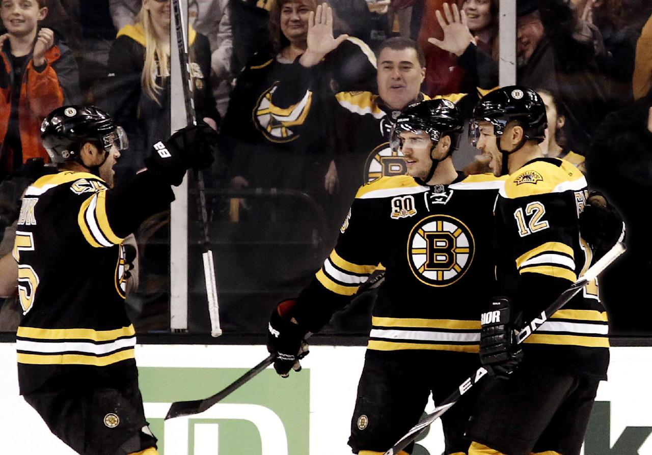 Boston Bruins' David Krejci, center, is congratulated by teammates Jarome Iginla (12) and Johnny Boychuk after his overtime goal gave the Bruins a 3-2 win over the Carolina Hurricanes in a NHL hockey game in Boston Saturday, Nov. 23, 2013. (AP Photo/Winslow Townson)