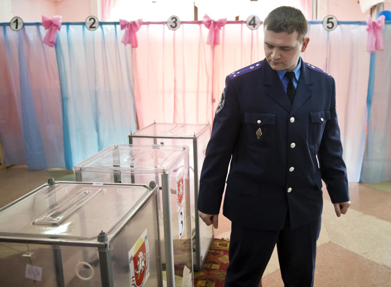 A Ukrainian policeman looks at ballot boxes after casting his vote in Perevalne, Ukraine, Sunday, March 16, 2014. Residents of Ukraine's Crimea region are voting in a contentious referendum on whether to split off and seek annexation by Russia. (AP Photo/Vadim Ghirda)