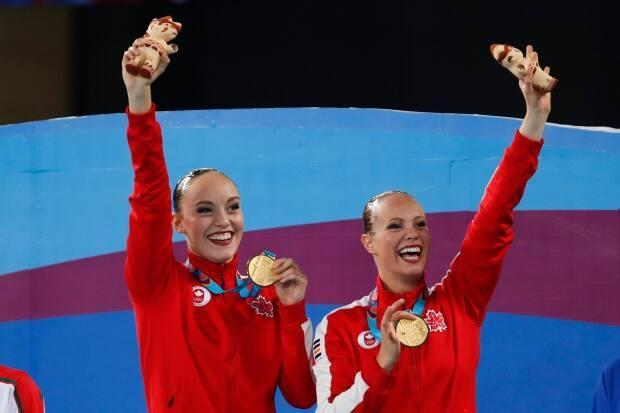 Jacqueline Simoneau, right, and Claudia Holzner, of Canada, celebrate after receiving their gold medals in the artistic swimming duet free routine finals at the Pan American Games in Lima, Peru on July 31, 2019. (Moises Castillo/The Associated Press - image credit)