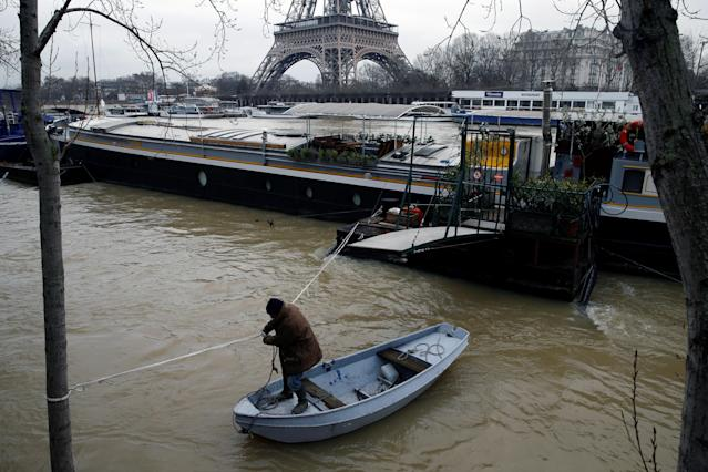 <p>A man uses a small boat to make his way from a houseboat as the Seine River overflows its banks as heavy rains throughout the country have caused flooding, in Paris, France, Jan. 26, 2018. (Photo: Pascal Rossignol/Reuters) </p>