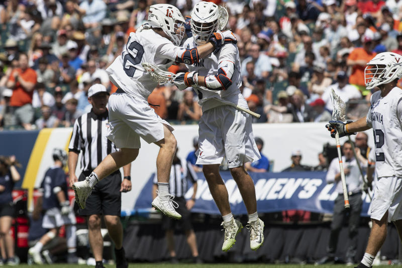 Virginia's Jack Simmons (12) congratulates Matt Moore after scoring in the fourth quarter of a game against Yale in the NCAA college lacrosse championship in Philadelphia on Monday, May 27, 2019. Virginia beat defending champion Yale, 13-9, in the national title game Monday. (Jose F. Moreno/The Philadelphia Inquirer via AP)