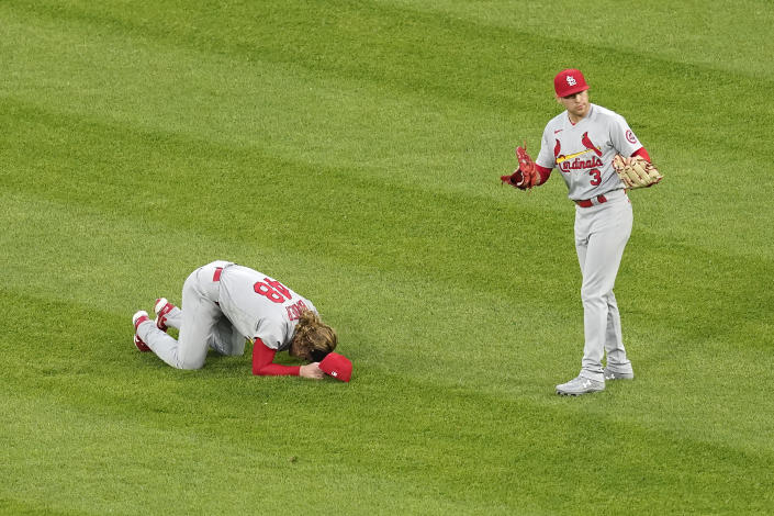 St. Louis Cardinals' Harrison Bader, left, stays on the ground as Dylan Carlson (3) signals the bench after Bader was unable to make a diving catch of a shallow fly ball by Chicago White Sox's Nick Madrigal during the third inning of an interleague baseball game Monday, May 24, 2021, in Chicago. (AP Photo/Charles Rex Arbogast)