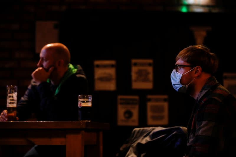 People watch the TV as Britain's Prime Minister Boris Johnson makes a speech, at a pub, amid the outbreak of the coronavirus disease (COVID-19) in Liverpool