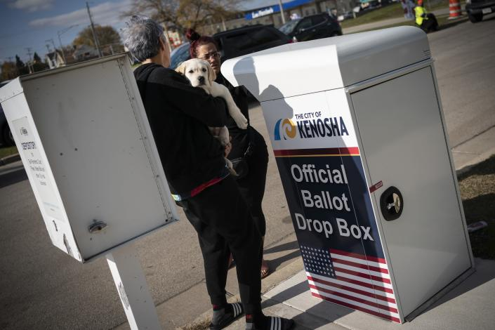 A woman carries her puppy as she drops off her ballot at Kenosha's municipal offices for early voting in Kenosha, Wis., Friday, Oct. 30, 2020. Trump has made protest violence in Kenosha and other American cities, a key part of his re-election campaign, linking violence to Democrats and saying it would spread dramatically if Democratic nominee and former Vice President Joe Biden was to defeat him on Election Day. (AP Photo/Wong Maye-E)