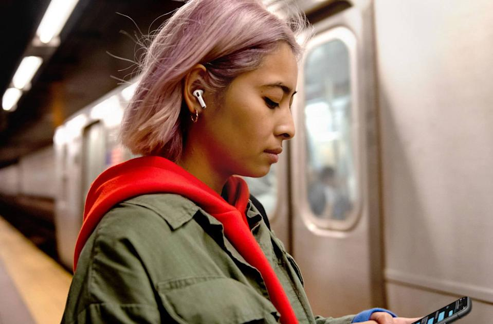 woman wearing a pair of Apple Airpods Pro waiting for a train on platform