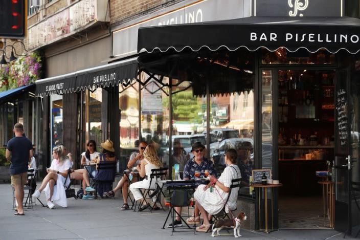 Customers practice social distancing in outdoor seating at a restaurant in New York City