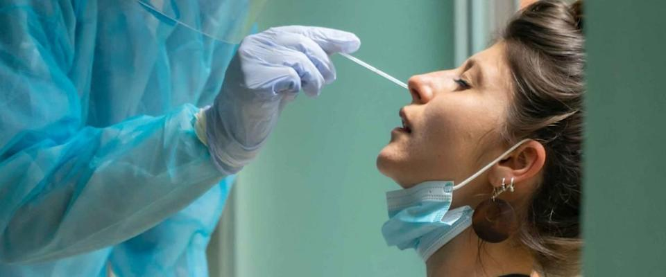 Healthcare worker with protective equipment performs coronavirus swab on Caucasian girl.Nose swab for Covid-19.