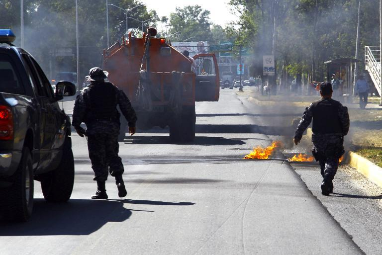 Firefighters and members of the state police rush to put out petrol bombs on Gomez Morin Avenue in Guadalajara, Jalisco state, Mexico, on May 1, 2015