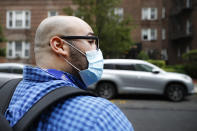 Joseph Ortiz, a contact tracer with New York City Health + Hospitals, heads to a potential COVID-19 patient's home Thursday, Aug. 6, 2020, in New York. The city has hired more than 3,000 tracers and the city says it's now meeting its goal of reaching about 90% of all newly diagnosed people and completing interviews with 75%. (AP Photo/John Minchillo)