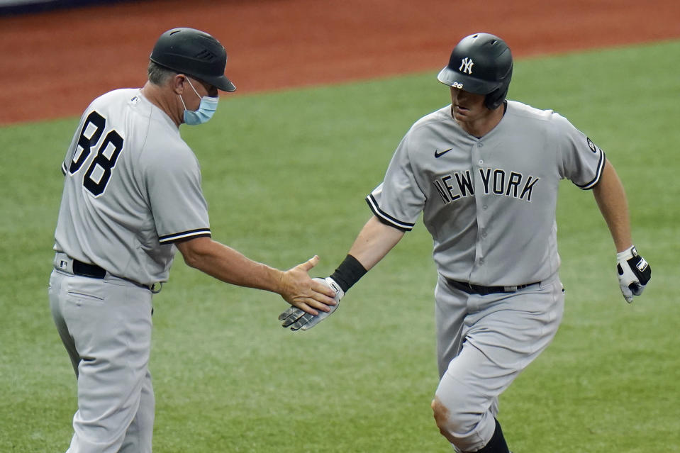 FILE- In this April 9, 2021, file photo, New York Yankees' DJ LeMahieu celebrates with third base coach Phil Nevin (88) after his home run off Tampa Bay Rays pitcher Hunter Strickland during the eighth inning of a baseball game in St. Petersburg, Fla. The Yankees announced Tuesday, May 11, 2021, that Nevin, who is fully vaccinated, has tested positive for the coronavirus. He is currently under quarantine protocol in Tampa. Under Major League Baseball's guidance and advice, and with its assistance, additional testing and contact tracing are ongoing. (AP Photo/Chris O'Meara, File)