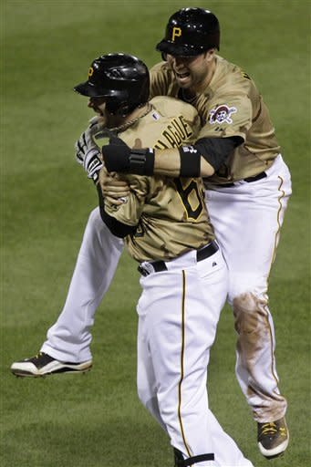 Pittsburgh Pirates' Matt Hague, left, celebrates with teammate Neil Walker after forcing in the game-winning run by being hit by a pitch from Chicago Cubs pitcher Rafael Dolis with bases loaded in the ninth inning of a baseball game in Pittsburgh, Saturday, May 26, 2012. The Pirates won 3-2. (AP Photo/Gene J. Puskar)