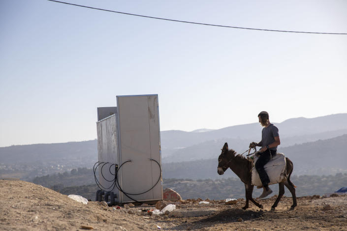 An Israeli settler rides a donkey in the recently established wildcat outpost of Eviatar near the northern Palestinian West Bank city of Nablus, Monday, June 28, 2021. Palestinians say the outpost was established on private farmland. Israeli media said Monday that the government was working on reaching a compromise with the settlers that would see the outpost evacuated in the coming days. (AP Photo/Ariel Schalit)