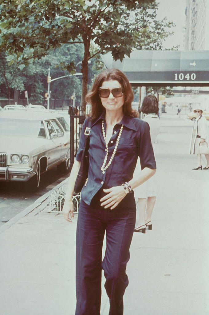 <p>Jackie' go-to uniform still resonates today: Oversize sunglasses, a navy button-down and matching pants, and yellow gold jewelry make for a classic look-about-town.<br></p>