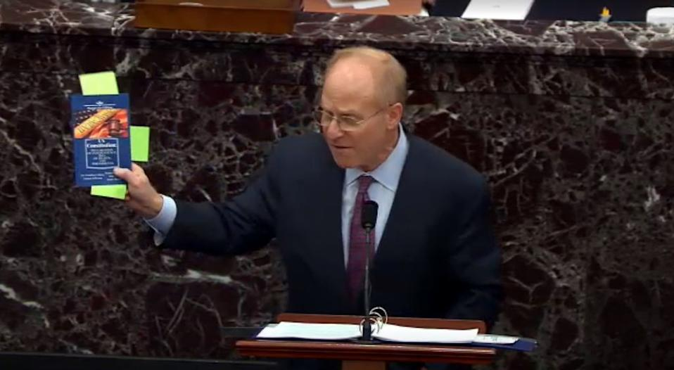 David Schoen, speaks while holding a copy of the Constitution.
