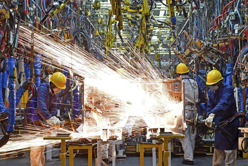 Employees work along a production line at a factory of Dongfeng Nissan Passenger Vehicle Co. in Zhengzhou