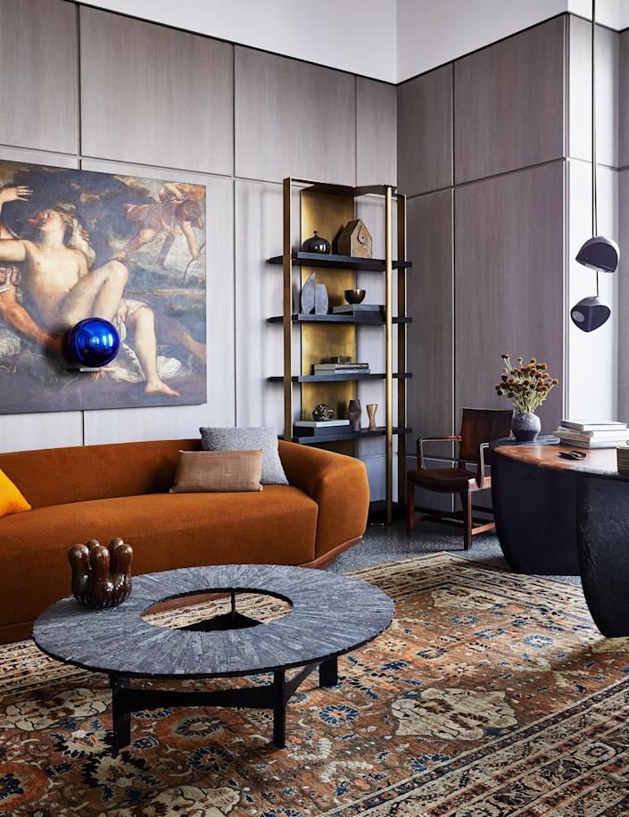In the husband's office, an artwork by Jeff Koons hangs above a custom sofa in a Rogers & Goffigon Wool. Pia Manu cocktail table; Kaare Klint chair from Dienst + Dotter; antique Persian Rug.