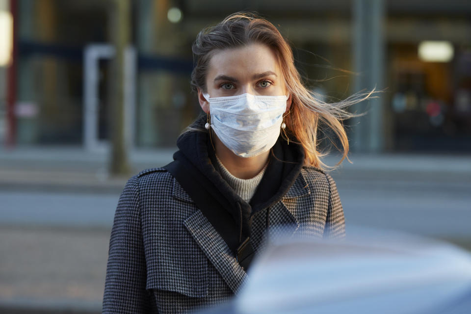 Young woman standing on city street wearing protective face mask