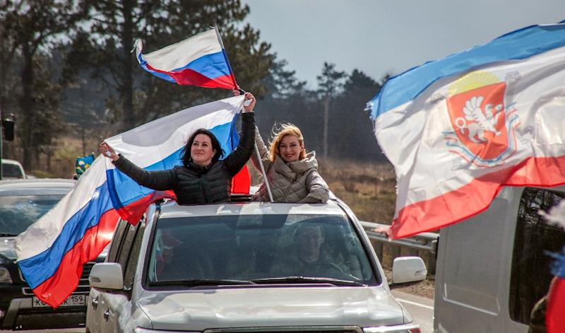 Women in Crimea wave Russian flags to celebrate the fifth anniversary of Moscow's annexation of the peninsula (AFP Photo/STR)