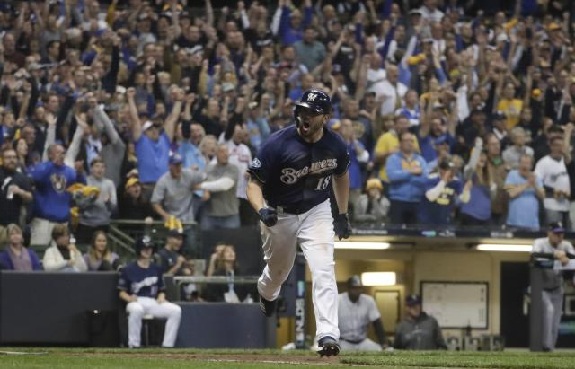 Milwaukee Brewers' Mike Moustakas reacts after hitting an RBI single during the eighth inning of Game 2 of the National League Divisional Series baseball game against the Colorado Rockies Friday, Oct. 5, 2018, in Milwaukee. (AP Photo/Morry Gash)