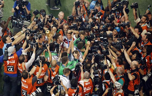 German players are mobbed by media after winning the World Cup final soccer match between Germany and Argentina at the Maracana Stadium in Rio de Janeiro, Brazil, Sunday, July 13, 2014. Mario Goetze volleyed in the winning goal in extra time to give Germany its fourth World Cup title with a 1-0 victory over Argentina on Sunday. (AP Photo/Fabrizio Bensch, Pool)