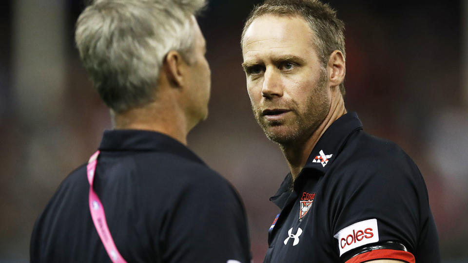 Ben Rutten, pictured here speaking with Essendon assistant coach Blake Caracella.