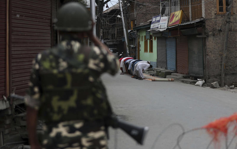 An Indian paramilitary soldier stands guard as Kashmiri Muslims offer Friday prayers on a street outside a local mosque during curfew like restrictions in Srinagar, India, Friday, Aug. 16, 2019. India's government assured the Supreme Court on Friday that the situation in disputed Kashmir is being reviewed daily and unprecedented security restrictions will be removed over the next few days, an attorney said after the court heard challenges to India's moves. (AP Photo/Mukhtar Khan)