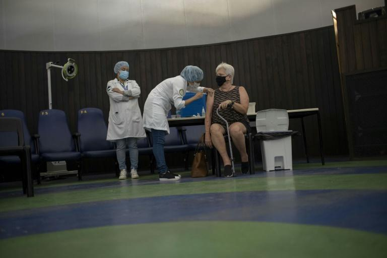 A woman is vaccinated against the coronavirus at Rio de Janeiro's Public Planetarium in March 2021