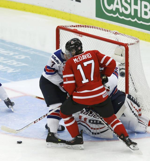 Canada's Connor McDavid (17) gets the puck just before scoring past United States' Nic Kerdiles and United States' goalie Jon Gillies during the third period of their IIHF World Junior Championship ice hockey game in Malmo, Sweden, December 31, 2013. REUTERS/Alexander Demianchuk (SWEDEN - Tags: SPORT ICE HOCKEY)