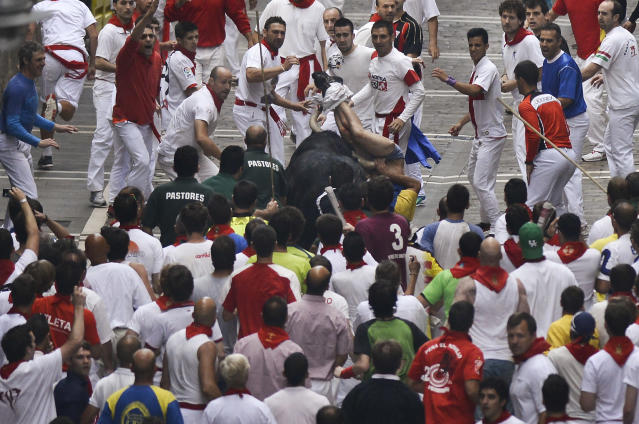"""A runner is gored by an """"El Pilar"""" fighting bull during the running of the bulls at the San Fermin festival, in Pamplona, Spain, Friday, July 12, 2013. Revelers from around the world arrive to Pamplona every year to take part in some of the eight days of the running of the bulls glorified by Ernest Hemingway's 1926 novel """"The Sun Also Rises."""" (AP Photo/Alvaro Barrientos)"""