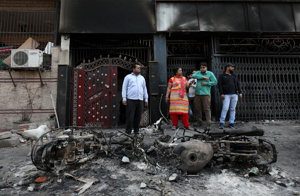 People stand next to the wreckages of motorcycles that were set on fire by a mob in a riot affected area after clashes erupted between people demonstrating for and against a new citizenship law in New Delhi, India, February 26, 2020. REUTERS/Rupak De Chowdhuri