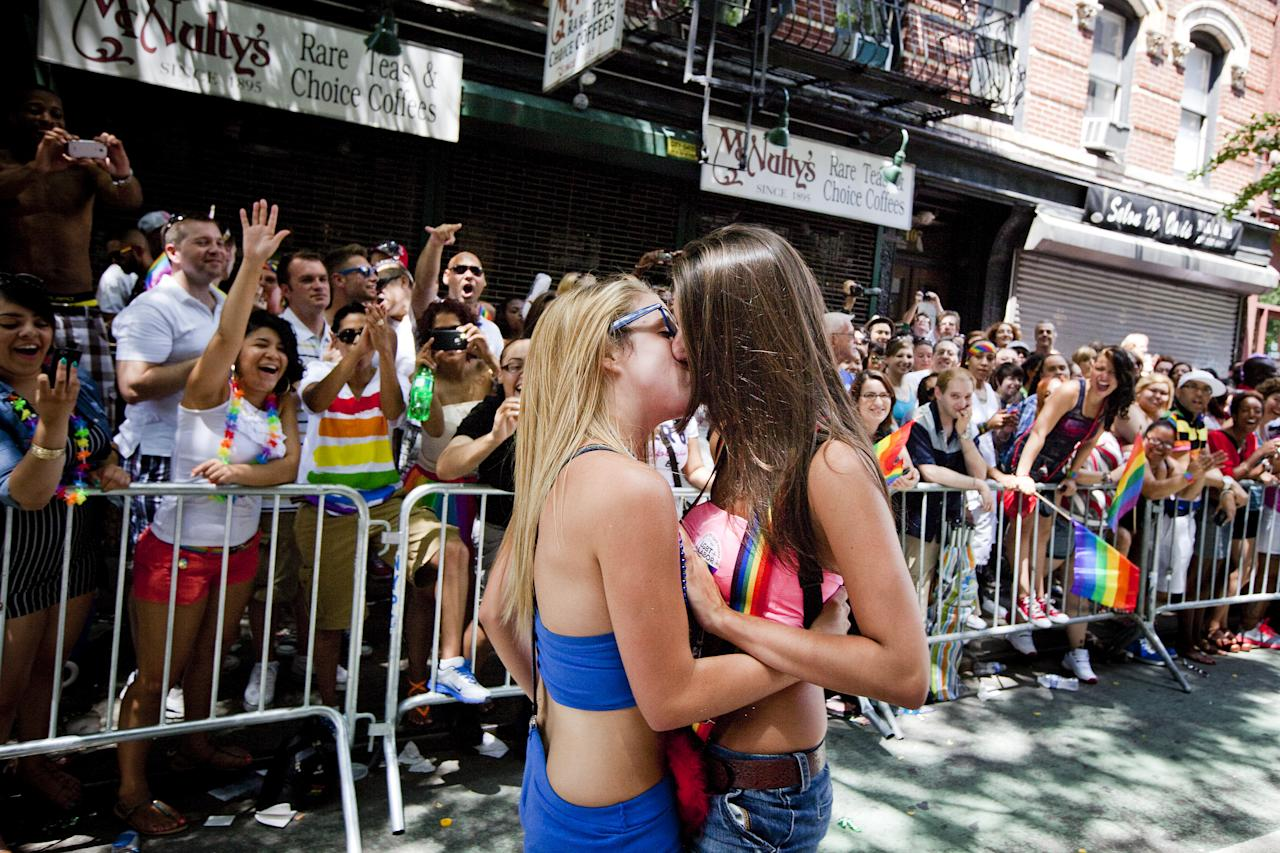 NEW YORK - JUNE 24:   Tess Reid (L) kisses Brianna Bono, both 17 years-old, during the New York City Gay Pride March on June 24, 2012 in New York City.  The annual civil rights demonstration commemorates the Stonewall riots of 1969, which erupted after a police raid on a gay bar, the Stonewall Inn on Christopher Street.  (Photo by Michael Nagle/Getty Images)
