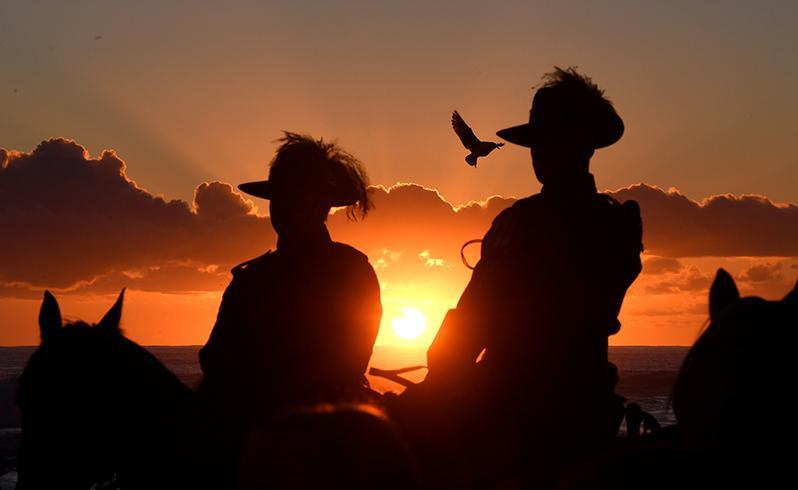 Horsemen stay on their mounts during the Anzac Day Dawn Service held by the Currumbin RSL is seen at Elephant Rock on Currumbin Beach, Gold Coast. Source: AAP