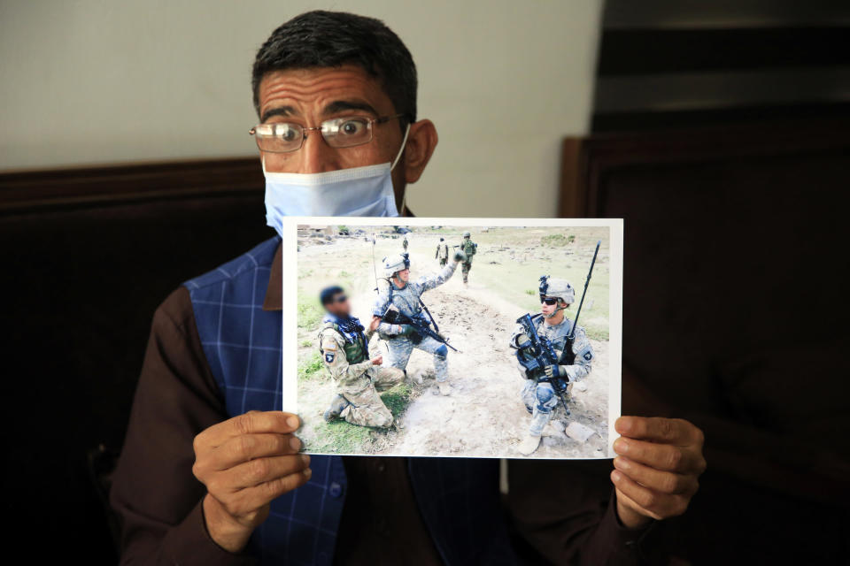 In this Friday, April 30, 2021, photo Ayazudin Hilal, 40, a former Afghan interpreter for the U.S. show his picture with the US Army soldiers during an interview to The Associated Press after a protest against the U.S. government and NATO in Kabul, Afghanistan. (AP Photo/Mariam Zuhaib)