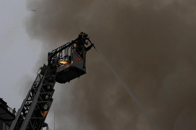 <p>Firefighters spray on fire from above as a helicopter flies even higher above at Tsukiji Fish Market on Thursday, Aug. 3, 2017, in Tokyo. (Photo: Sherry Zheng/AP) </p>